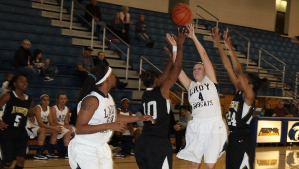 """""""Georgia Northwestern All-Region sophomore Emily Cole (Adairsville, GA) climbs high Tuesday night to find freshman post Odessa Person (Lineville, AL) down low in the Lady Cats come-from-behind win over West Georgia Tech at the Winthrop-King Center in Rome, Georgia."""""""