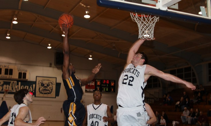 """Welch College (TN) junior Kendred Sides gets a rude welcoming in the paint as sophomore NJCAA All-Region and All-District First-Teamer Alex Miller (Calhoun, GA) flies high to reject the shot attempt Tuesday night at The R.A.C. (Rossville Athletic Complex)"""