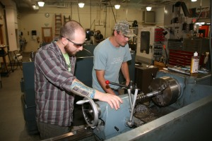 Brian Pierce (left) and Brooks Cain (right) work on a lathe machine in the shop for GNTC's Machine tool Technology program. Pierce and Cain both served as specialist in the U.S. Army and knew each other before they entered the program.