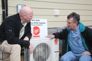 John Anderson (right), owner of John Anderson Service Company, Inc., and Donny Holmes (left), director of GNTC's Residential Energy Efficiency program, put the finishing touches on the installation of a mini-split heat pump system.