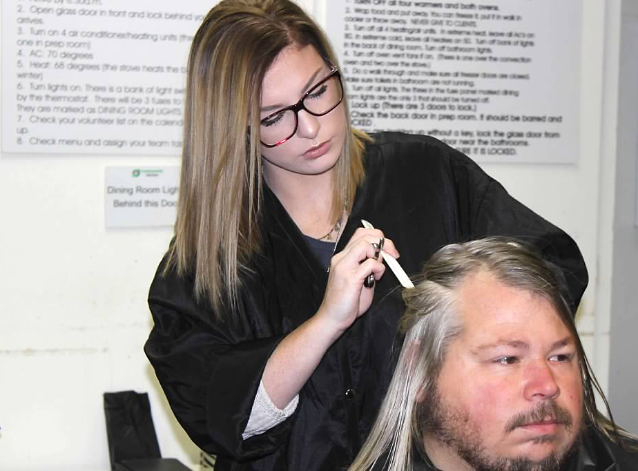 GNTC Cosmetology student Aubri Gazaway gives a client a haircut at the William s. Davies Homeless Shelter.