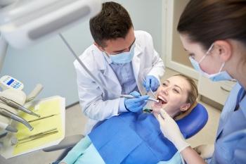 male dentist treating female patient teeth